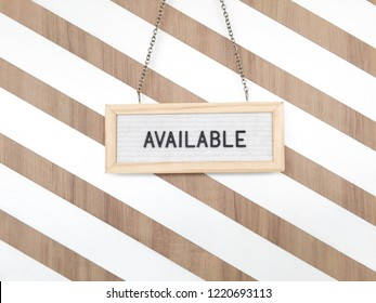 """The sign with the text of """" AVAILABLE"""" hang in front of the door with white strip background on wooden material with copy space"""