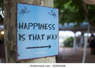 """Sign with the text """"Happiness is that way"""""""