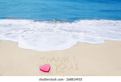 "Sign ""Thank you"" on the sandy beach next to ocean"