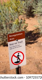 """A sign that reads, """"Revegetation Area Stay on Trail"""" on desert path in the  Colorado National Monument, near Fruita, Colorado.  The sign is to protect fragile cryptobiotic soil."""