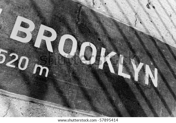 A sign that reads BROOKLYN on a placard mounted in the concrete.  You can see the shadows from the bridge wires.