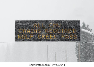 Sign that says All CMV Chains required Wolf Creek Pass in a blizzard