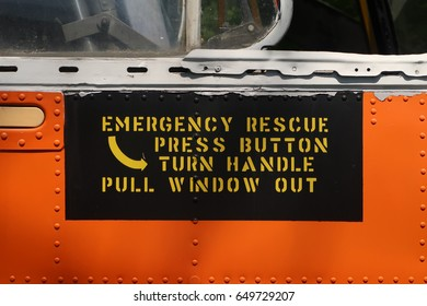 "Sign that says, ""EMERGENCY RESCUE PRESS BUTTON TURN HANDLE PULL WINDOW OUT."