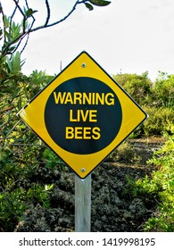 A sign warning abot live bees in the area, perimeter of an apiculture farm.