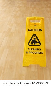 Sign warning of cleaning in progress on a wet floor.