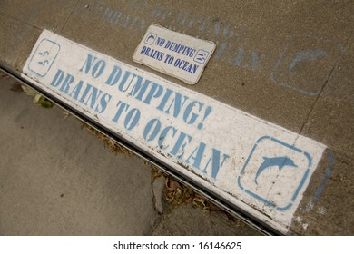 A sign warning not to dump into the street gutter, as it drains to the ocean.