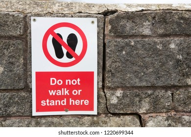 Sign warning people not to walk or stand near the wall.