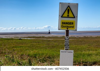 a sign warning of quicksand with the seashore and lighthouse ion the background