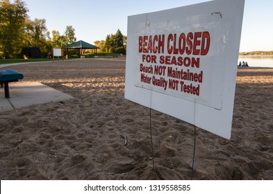 Sign warning swimmers that the beach is closed for the season, water quality is not tested. Taken in fall