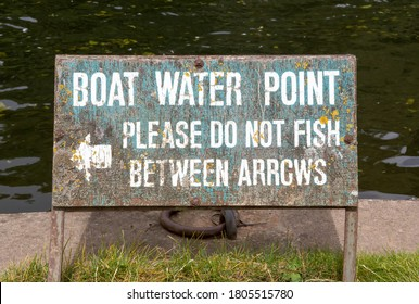 Sign warning that no fishing is allowed between the arrows at a boat water point.