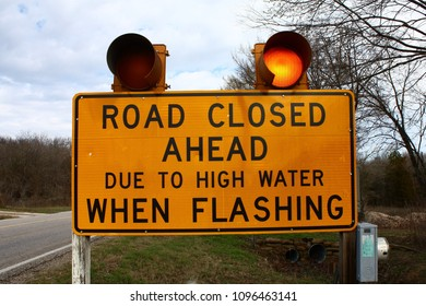 A sign warning that road is closed due to flooding.