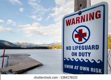 Sign warning that there is no lifeguard on duty at near a frozen winter lake.