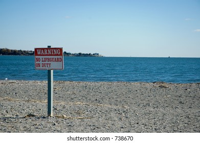 Sign warning that there is no lifeguard on duty at the beach.  Focus on Sign.
