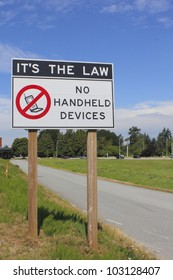 A sign warns that using handheld devices while driving is not permitted/No Handheld Devices Permitted/A sign warns drivers not to use handheld devices
