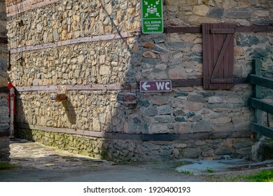 """Sign of WC and muster point with green board hanging on ancient and old style wall. translation of  words in green tabella is """"muster point"""".  - Shutterstock ID 1920400193"""