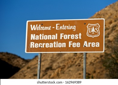 Sign welcomes visitors to a Recreation Fee Area of a National Forest.