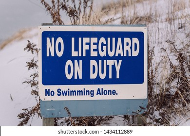 "Sign in the winter beach stating ""No Lifeguard on  Duty.  No Swimming Alonge"""