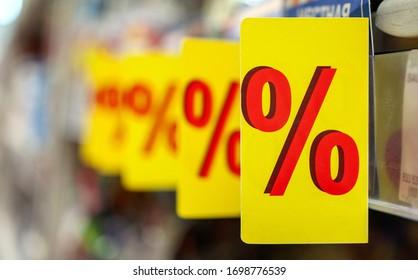 """Kennzeichnung der Formulierung """"%"""" im Regal des Verbrauchers im Supermarkt. """"%""""-Label (Tag), Symbol der besonderen Werbung als Konzept des Angebots von Produkten zu reduzierten Preisen. Regale auf unscharfem Hintergrund."""
