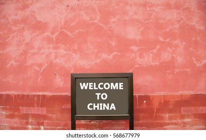 Sign with the words Welcome to China in front of an ancient red wall in the Forbidden City in Beijing, China