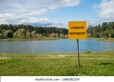 Sign with writing 'Swimming is prohibited' (on Russian) near coast of reserved freshwater lake, mixed forest of birches & pines is on background. Picture taken on Lebyazhye (Swan) lake, Kazan, Russia