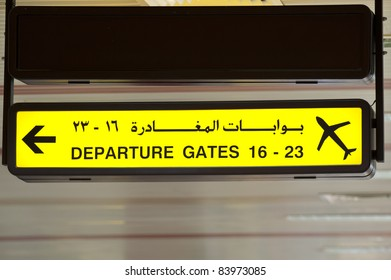 A sign written in both Arabic and English language indicating departure gates at an airport.