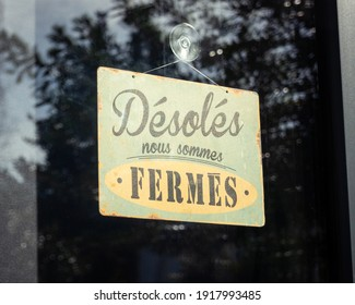 Sign written in French on shop window reads 'sorry, we are closed', in France