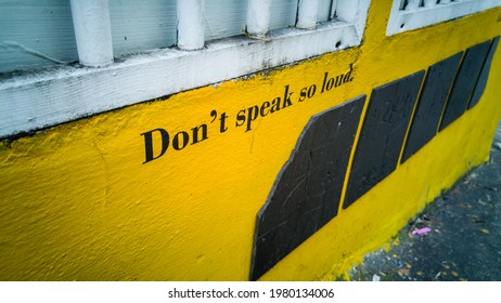 A sign written on a yellow wall says Don't speak so loud