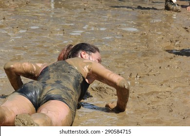 SIGNA, ITALY - MAY 9 2015: A woman lie down in the mud during the Mud Run competition near Florence on May 2015