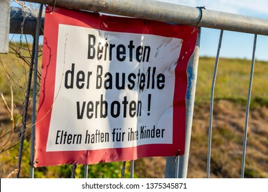 "Signage of a construction site at a fence: Translation: German for ""Enter the construction site prohibited! Parents are responsible for their children"""