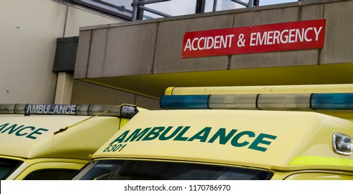 The signage on two NHS ambulances parked underneath an Accident and Emergency sign at a hospital in the UK