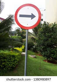 Signage plate, galvanized steel plate, with electrostatic paint, reflective adhesive, in the central region of Brasilia, in the middle of a beautiful garden, indicating the direction to follow.