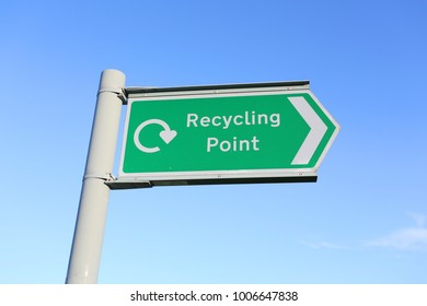 signage for recycling shot against a blue sky with symbol and english words