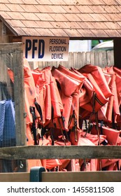 signage that reads PFD Personal Floatation Device and several  orange life jackets hung in two rows in a wooden hanging hut