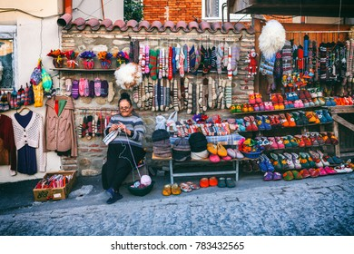 Signagi, Georgia - 20 April, 2017: Woman female vendor sells and knits woolen slippers and socks felted bright souvenir in the street of Sighnaghi or Signagi town, Kakheti region, Georgia