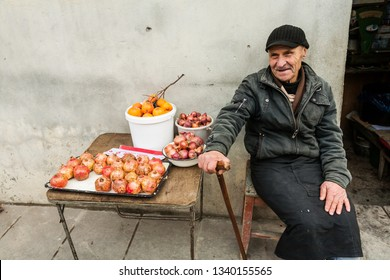 Signagi, Georgia - november 23, 2011: Old man selling pomegranates , onion and persimmon on a  street in Signagi, Georgia