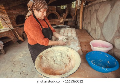 SIGNAGI, GEORGIA - OCT 7: Older woman baking homemade bread in her house kitchen in rural village style with stone oven on October 7, 2016. Signagi of Kakhetia has a population 2.200