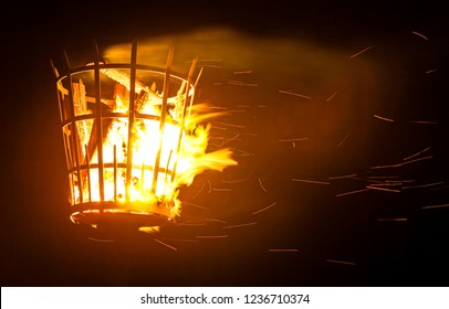 A signal beacon on fire with smoke and sparks.
