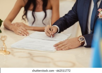 Signature Ceremony. Cropped close up photo image of wedding couple hands with pen, paper document state marriage registration authority, town council or city hall. Wedding tradition custom.