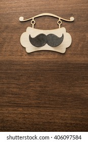 signboard with black paper mustache, happy fathers day in italian, against a brown wooden table background. Empty space for inscription.