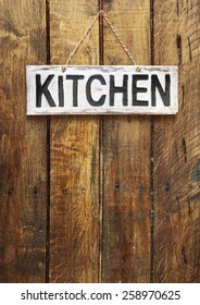 "signboard ""kitchen"" on a wooden background"