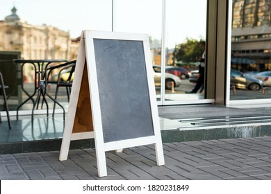 Signboard on the street. Empty menu board stand. Restaurant sidewalk chalkboard sign board. Freestanding A-frame blackboard near outdoor cafe. Selective focus