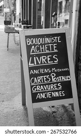 Signboard outside old books store in France. Text in French meaning: Secondhand bookseller buying old and modern books, postcards, ancient prints. Aged photo. Black and white.