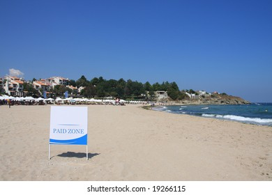 """Signboard """"Paid zone"""" on the beach."""