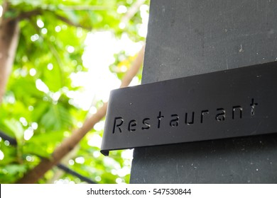 Signboard of restaurant text on the black wall