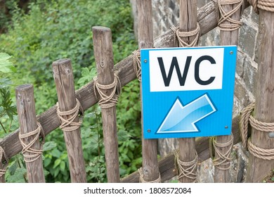 Signboard for WC hanging on wooden fence for toursits.