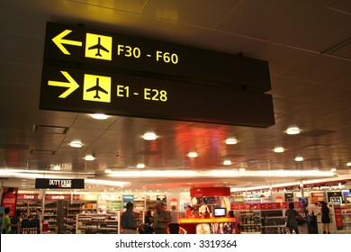 Signboards at the airport showing direction of the boarding gates while passengers shop in the background.
