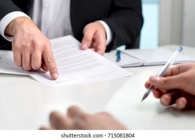 Signing a contract or agreement. Banker or lawyer showing client the line for autograph in a document paper. Business man with a customer in office making deal. Employee hired.