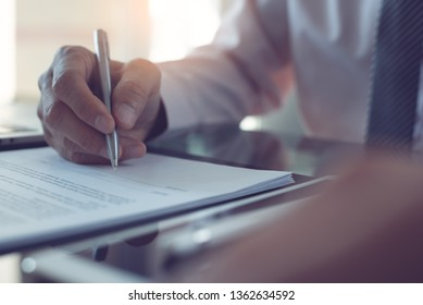 Signing contract, business agreement, deal concept. Business man signing official contract, formal document with a pen and digital tablet computer on desk in office with morning sunlight, close up