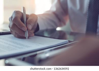 Unterzeichnung des Vertrags, Geschäftsvereinbarung, Deal-Konzept. Geschäftsmann, der einen offiziellen Vertrag unterzeichnet, formelles Dokument mit einem Schreibtisch und einem digitalen Tablet-Computer auf dem Schreibtisch mit Morgensonnenlicht, Nahaufnahme
