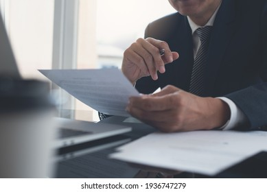 Signing contract, business agreement and deal concept. Closeup businessman reading business contract documents at desk with laptop computer, busy with paperwork. Man manager proofing report at office
